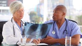 Ernstig medisch team die een borströntgenstraal bekijken stock video