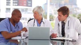 Ernstig medisch team die laptop bekijken stock footage