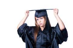 Ernstig meisje in graduatiekleding op isolate Stock Foto