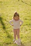 Ernstig meisje Het spel van het kindmeisje met paardstuk speelgoed op groen gras stock afbeelding