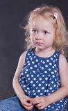 Ernstig meisje 3 jaar oud, op donkere achtergrond. Stock Afbeeldingen