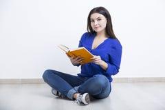 Ernstig meisje in jeans met een boek royalty-vrije stock foto