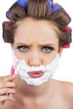Ernstig model in haarkrulspelden die met het scheren van schuim en scheermes stellen Stock Afbeeldingen