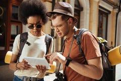 ernstig multicultureel paar van toeristen met het digitale tablet kijken stock foto