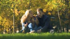 Ernstig paar die in de zitting van het de herfstpark op plaid spreken, die verhouding bespreken stock videobeelden