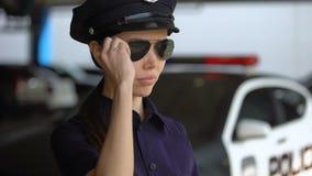 Ernstig patrouillerende politieagente in politie het eenvormige zetten op zonnebril, klaar voor plicht stock footage