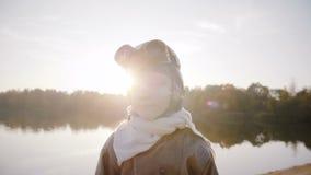 Ernstig portret van weinig jongen die camera in retro proefglazen dichtbij zonsondergangmeer bekijken met backlight langzame moti stock video