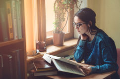 Ernstig vrouwelijk de lezingsboek en zitting van de hipsterstudent bij de bruine lijst in openbare universitaire bibliotheek Jong Royalty-vrije Stock Foto