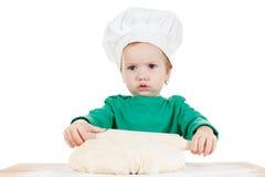 Ernstig weinig die jongen het kneden deeg voor de koekjes, op wit worden geïsoleerd royalty-vrije stock afbeeldingen