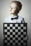Ernstig Weinig jongen met schaakbord Fashion Children Vlinderdas Weinig geniekind Stock Afbeelding