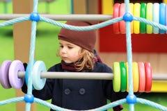 Ernstige éénjarigenmeisje in een bruine hoed en het donkerblauwe laag spelen met houten kleurrijke cirkels op de de herfstspeelpl stock fotografie