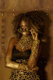 Ernstige Afrikaanse jonge vrouw met een afrokapsel die zonnebril en gouden manierstylization dragen Stock Afbeeldingen