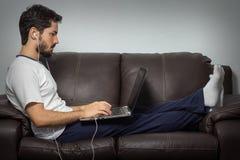 Ernstige arbeider bij zijn huisbureau werken die met laptop werken Stock Afbeeldingen