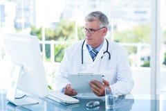 Ernstige arts die aan computer bij zijn bureau werken Stock Fotografie
