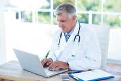 Ernstige arts die aan laptop bij zijn bureau werken Stock Afbeelding