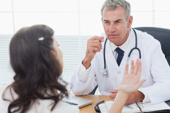 Ernstige arts die aan zijn het geduldige spreken luisteren stock foto's
