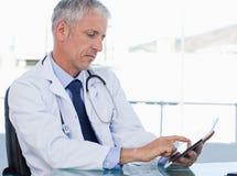 Ernstige arts die met een tabletcomputer werkt stock foto