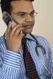 Ernstige arts die op mobiele telefoon spreekt Stock Fotografie
