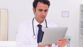 Ernstige arts die zijn tabletpc met behulp van stock footage