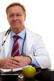 Ernstige arts in zijn bureau stock afbeelding