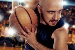 Ernstige basketbalspeler met bal in de spelactie Stock Foto