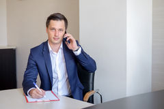 Ernstige bedrijfsmens in bureau die celtelefoongesprek maken en nota's nemen Stock Afbeeldingen