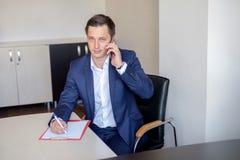 Ernstige bedrijfsmens in bureau die celtelefoongesprek maken en nota's nemen Stock Fotografie