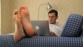 Ernstige bedrijfsmens die op bank liggen, die met peinzend laptop werken, voeten, close-up stock video
