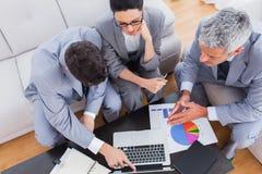 Ernstige bedrijfsmensen gebruikend laptop en samenwerkend aan bank Stock Foto