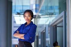 Ernstige bedrijfsvrouw die zich buiten de bureaubouw bevinden Royalty-vrije Stock Foto