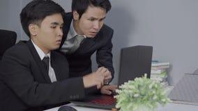 Ernstige beklemtoonde twee bedrijfsmens die een laptop computer met behulp van aan het werk project stock footage