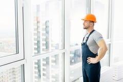 Ernstige bouwingenieur die zich dichtbij venster bevinden royalty-vrije stock foto's