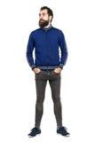 Ernstige gebaarde hipster in bovenkledijjasje met dient zakken in weg kijkend Royalty-vrije Stock Foto