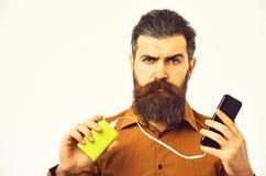 Ernstige gebaarde mens hipster het laden celtelefoon met machtsbank stock afbeelding