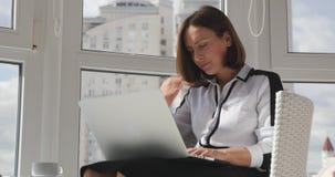 Ernstige gerichte jonge zakenvrouw in witte blouse en bril die haar ogen sluit, nadenkt over fouten op het werk en boos is stock footage