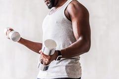 Ernstige goed-bouwstijl Afrikaanse atleet die met baard training met handgewichten uitvoeren Royalty-vrije Stock Afbeelding