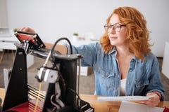 Ernstige harde werkende vrouw die een knoop op de 3d printer drukt Stock Afbeelding