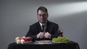 Ernstige heer in de kostuumzitting bij de kleine lijst voor vrede van vlees, druiven, appelen, rode wijn en kaarsen stock video