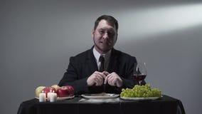 Ernstige heer in de kostuumzitting bij kleine lijst voor vrede van vlees, druiven, appelen, rode wijn en kaarsen stock videobeelden