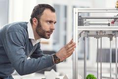 Ernstige jonge ingenieur die 3D printer van plaats veranderen Stock Fotografie