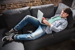 Ernstige jonge mens die op bank liggen en laptop, kleine bedrijfsmensenconcept met behulp van Stock Foto