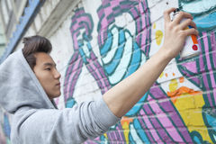 Ernstige jonge mens die terwijl in openlucht het houden van een aërosol en nevel het schilderen op een muur concentreren zich Stock Foto