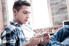 Ernstige jonge mens die vrijetijdskleding dragen en het scherm van zijn apparaat bekijken stock fotografie