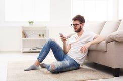 Ernstige jonge mens thuis met mobiel royalty-vrije stock foto