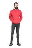 Ernstige jonge punker in rood sweatshirt die met een kap weg eruit zien stock foto