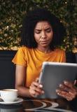 Ernstige jonge vrouw die digitale tablet in koffie gebruiken royalty-vrije stock foto