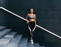 Ernstige jonge vrouw in sportkleding die zich bij een muur bevinden Royalty-vrije Stock Afbeeldingen