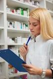 Ernstige jonge vrouwelijke apotheker die een klembord houden stock afbeelding