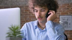Ernstige jonge zakenman met volume krullend haar die aan laptop werken en op telefoon spreken, die in modern bureau zitten stock footage