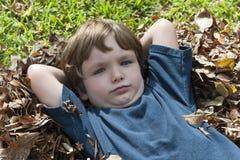 Ernstige jongen in bladeren stock afbeeldingen